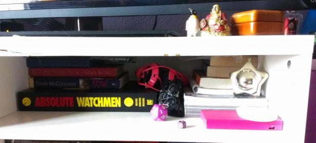 One of my entertainment center shelves, more random things including my DSi and Absolute Watchmen comic book.