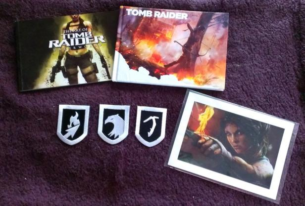 Some of my random Tomb Raider collectibles including two artbooks, patches, and a lithograph.