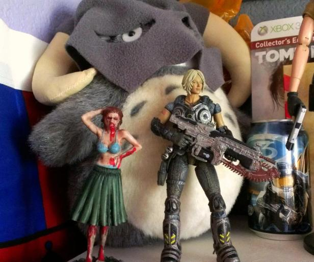 That's a Totoro plushie in a Dovakhiin hat next to Anya Stroud from Gears of War 3 and a zombie hula girl.
